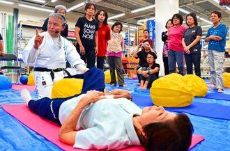 バランスボールを使った体のほぐし方を教える池原英樹氏(手前左)=17日、メイクマン浦添本店