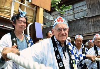 法被に鉢巻き姿で御白石持行事に参加した、日本文学研究者のドナルド・キーンさん(中央)=2013年8月、三重県伊勢市