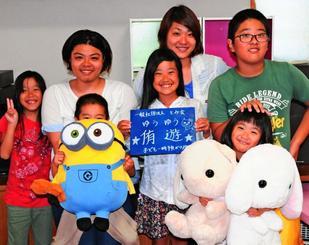 「ひとり親の子どもも親も支援したい」と話す金城里奈さん(後列左から2人目)と麻希さん(同3人目)姉妹。麻希さんの子どもたちも事業を応援している=7日、南城市大里