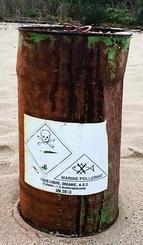 国頭村安田の海岸に漂着したドラム缶。ドクロマークや「毒物」の英語表記がある(提供)