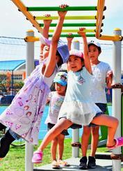青空の下、うんていを楽しむ子どもたち=4日、沖縄市・美東公園(落合綾子撮影)