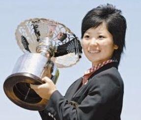 ゴルフの日本女子アマチュア選手権を制し、トロフィーを手に笑顔の比嘉真美子選手=6月25日、宝塚GC