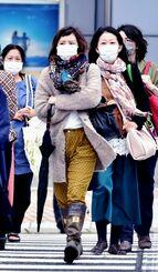 マフラーやコートを着て寒そうに歩く女性=4日午後5時ごろ、那覇市久茂地(国吉聡志撮影)