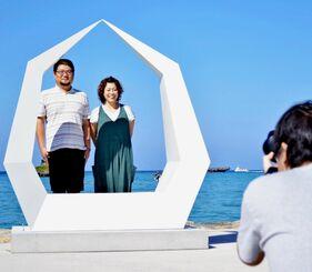 翁長瞳さん制作のオブジェ「祝福の鐘」で記念撮影する夫婦=22日、恩納村海浜公園ナビービーチ