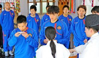 開幕を前に神酒で必勝を祈願するFC琉球の選手=那覇市の護国神社