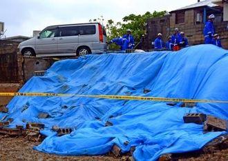 駐車場の一部が崩落し、被害拡大防止のため、ブルーシートがかぶせられた=1日午後1時50分ごろ、那覇市長田
