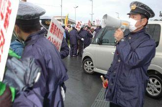 米軍キャンプ・シュワブ内に入る工事関係とみられる車両に抗議する市民と、それを制止する警察官ら=16日午前7時45分ごろ、名護市辺野古