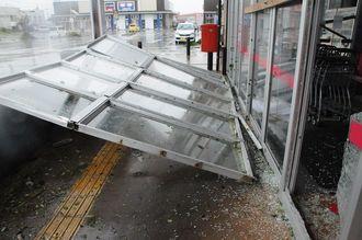台風18号の影響でドアの窓ガラスが割れ、看板も倒れたスーパー=14日午前9時8分、宮古島市平良
