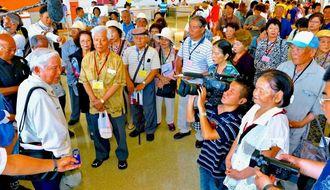 結団式で平良善一団長(手前左)のあいさつを聞く慰霊団=25日午前11時、那覇空港