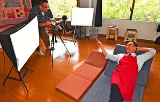 「すごいでしょ~」 本社の中にある撮影用の部屋で収録する「石嶺店長」=4月29日、沖縄市海邦町・ビッグワン本社
