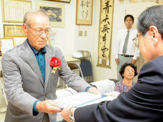 玉城中学校の卒業証書を受け取る諸見里安信さん(左)。中学卒業に「いま、すごく楽な気持ち」という=23日、南城市の同校