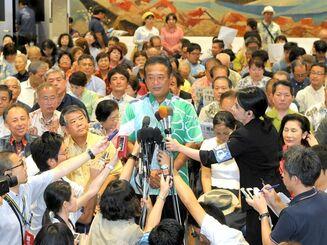 投票終了後、テレビの開票速報を見守る安里繁信氏=21日午後8時、那覇市牧志の選挙事務所