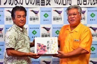 備蓄食として採用するパインあまがしの目録を手にPRする小川副村長(左)と安次富社長=11日、国頭村役場