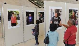 垂見健吾さんの「新琉球人の肖像」に見入る来場者=27日、那覇市久茂地・タイムスビル