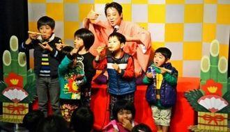 扇子を箸に見たて、子どもたちにそばを食べるしぐさを教える北山亭メンソーレさん(奥)=沖縄こどもの国