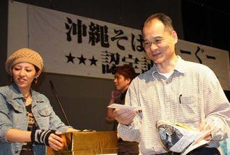 期間中に沖縄そば126杯をたいらげ、「親方」に選ばれた仲吉朝得さん(右)。名前入りのどんぶりがプレゼントされた=那覇市牧志のぶんかテンブス館