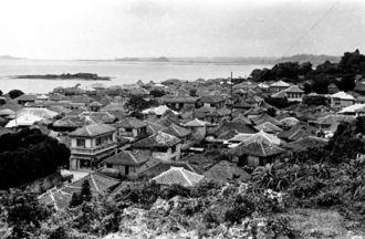 糸満中心部、山巓毛(さんてぃんもう)から北西の眺望。赤瓦の家並から、町の発展ぶりが伝わる。豊かさの源は漁業による収入だった。写真奥、左側の濃い島影は糸満で「アナギ」と呼ぶ島だが、1960年代の埋め立てで陸続きになった。アナギの一部だった岩は今も残り、拝所になっている(写真:朝日新聞社)