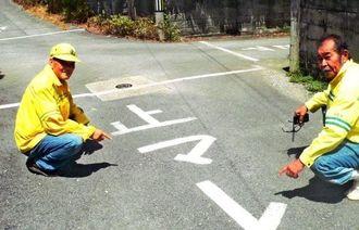 「止マレ」の道路標示を紹介する仲井間区長(左)と宮里会長=名護市仲尾次