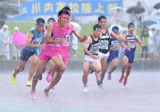 激しい雨の中、力走する南九州高校陸上大会の選手たち=14日午前、沖縄市・県総合運動公園陸上競技場(下地広也撮影)