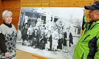 糸数アブチラガマ案内センターの當山晃事務局長(右)から写真の複写を受け取った島袋洋子さん。中央の写真パネルは展示用で、前列中央に島袋さんの親戚の照屋毅さんが写っている=南城玉城の同センター