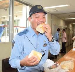 フランスパンにめんたいこゴボウサラダを挟んで食べる長嶺王公巡査部長=9月30日、那覇署