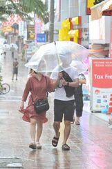 時折激しく降る雨の中、傘をさして歩く人たち=9日午後、那覇市・国際通り