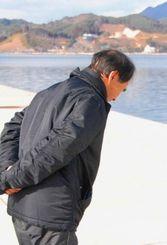 山田湾に向かって黙とうする漁師の亀山さん=日午後2時47分、岩手県山田町