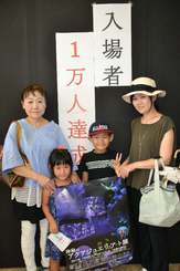1万人目の入場者となった(左から)石川美也子さん、友利桜子ちゃん、駿太郎くん、奈央さんのご家族=31日、豊見城市・アウトレットモールあしびなー