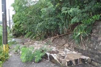 擁壁の一部や土砂が崩れ落ちた道路=20日午前6時55分、うるま市豊原