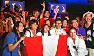 盛り上がるペルーの若者ウチナーンチュら。手前右は玉元三奈美実行委員長=23日、うるま市・勝連城跡