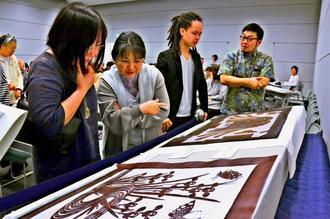 「糸掛け」の技法で紅型の型紙(手前)を制作した知念績人さん(右から2人目)=30日、那覇市の県立博物館・美術館