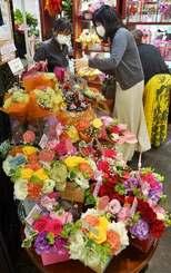 プレゼントの花を選ぶ買い物客=8日、那覇市久茂地・オランディアガーデン