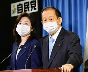 記者会見する自民党の二階幹事長。左は野田幹事長代行=25日午後、東京・永田町の党本部