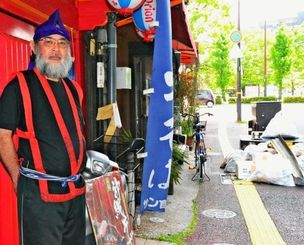 震災後、エイサーの衣装を着て店を再開させた新里博昭さん。店の前には震災でのがれきやごみが積まれている=22日、熊本市中央区・沖縄料理「ぬちぐすい」