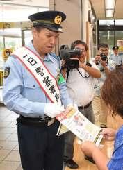 特殊詐欺防止のチラシを配る一日名護署長のパッション屋良さん=琉球銀行名護支店