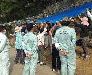 沖縄総合事務局の職員らが見つめる中、テントを再設置する市民ら=8日午前8時40分、名護市の米軍キャンプ・シュワブ前