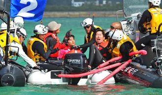 米軍キャンプ・シュワブ沿岸の工事に抗議する市民のボート(中央)を制止し、船外へ引き出そうとする海上保安官=15日午前9時5分ごろ、名護市辺野古(松田興平撮影)