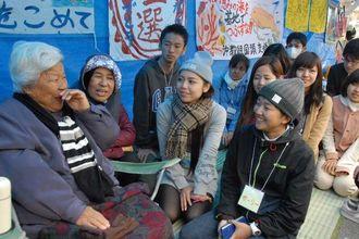 米軍キャンプ・シュワブゲート前を訪れ、辺野古の島袋文子さん(左)と歓談する学生ら=6日、名護市辺野古