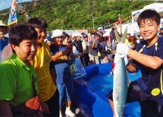 大物を捕まえて喜ぶ佐手小学校6年の上地光琉君(右)=国頭村・宜名真漁港