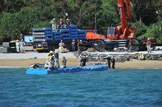 浮き桟橋状の資材が次々と海上に運ばれるキャンプ・シュワブの作業現場=27日午前9時55分ごろ、名護市辺野古沖