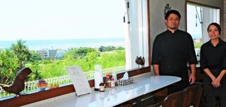大きな窓から久米島沖の海を望める「ゆくい処 笑島」店主の島袋航弥さんと、妻の愛佳さん