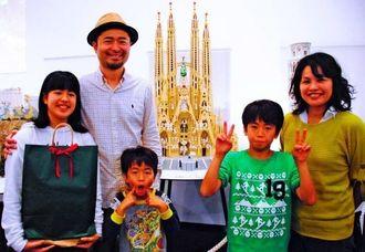 レゴで作られたスペインのサグラダファミリアを前に笑顔を見せる片野さん家族=3日、浦添市美術館