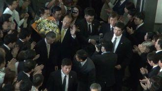 警察官にガードされ1階ロビーに姿を見せた仲井真知事。県職員が花道をつくって見送った=9日午前、沖縄県庁