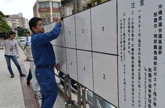 県議選のポスター掲示板を設置する関係者=12日午前、那覇市役所本庁舎前