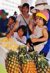 旬を迎えた石垣島産パインアップルを味わおうと詰め掛けた親子連れ=1日、石垣市新栄町・JAファーマーズマーケット「ゆらてぃく市場」