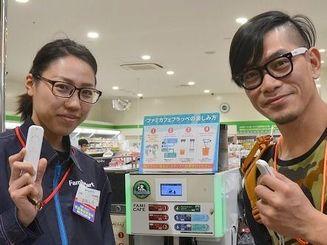自動翻訳機器「ili」でやりとりをするファミリーマートイオンモール沖縄ライカム店の大城佳奈さん(左)と台湾人観光客のワン・ホウクォンさん=27日、北中城村の同店