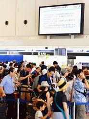 搭乗手続きの乗客でごった返すフロア。航空各社が大型モニターで発着便の遅れを知らせた=26日午後1時28分ごろ、那覇空港