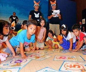 真剣な表情で「琉球いろはカルタ」に挑戦する子どもたち=3日午後、那覇市久茂地・タイムスホール