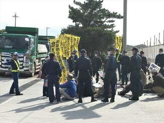 沖縄県名護市辺野古の新基地建設の埋め立て用土砂を搬入するダンプの前で座り込み抗議する市民と、市民を取り囲む機動隊=11日午前10時ごろ、名護市安和