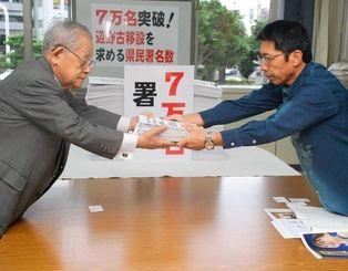 中地昌平会長(左)から署名を受け取る親川達男基地防災統括監=28日、県庁